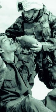 Man being given water by a soldier